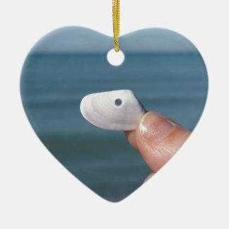 Ornamento De Cerâmica Guardarando um seashell na mão com mar azul