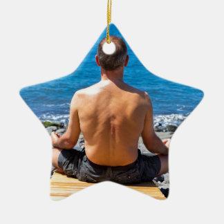Ornamento De Cerâmica Homem que meditating na praia e no mar