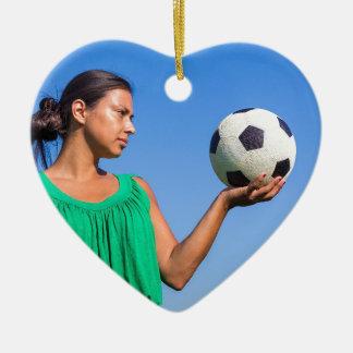 Ornamento De Cerâmica Jovem mulher que guardara o futebol na mão com céu