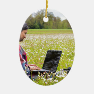 Ornamento De Cerâmica Mulher que senta-se com o laptop no prado do