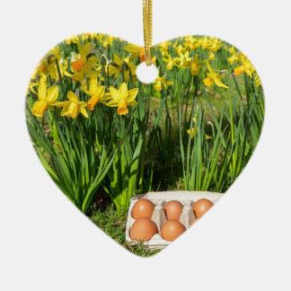 Ornamento De Cerâmica Ovos na caixa na grama com daffodils amarelos