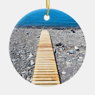 Ornamento De Cerâmica Passeio de madeira na praia que conduz ao mar