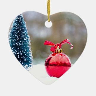 Ornamento De Cerâmica Poucos árvore de Natal e bauble vermelho na neve