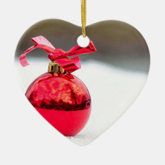 Ornamento De Cerâmica Uma bola vermelha brilhante do Natal fora na neve