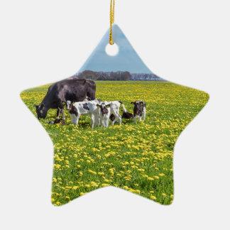 Ornamento De Cerâmica Vaca com as vitelas que pastam no prado com