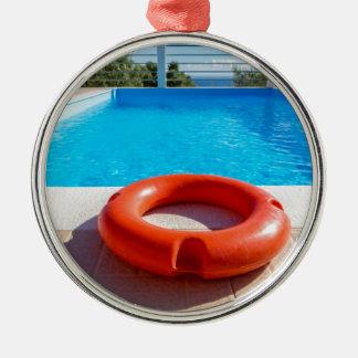 Ornamento De Metal Bóia de vida alaranjada na piscina azul