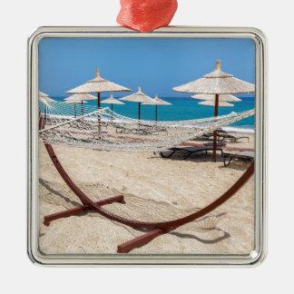 Ornamento De Metal Hammock com os guarda-chuvas de praia na costa