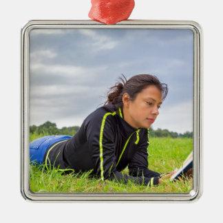 Ornamento De Metal Jovem mulher que encontra-se no livro de leitura