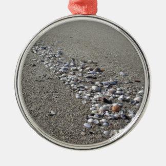 Ornamento De Metal Seashells na areia. Fundo da praia do verão