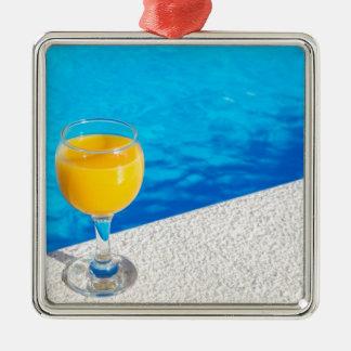 Ornamento De Metal Vidro com sumo de laranja na borda da piscina