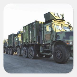 Os caminhões blindados sentam-se no cais na cidade adesivo quadrado