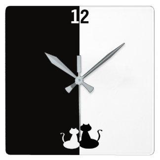 Os gatos brancos pretos do contraste oposto à relógio quadrado