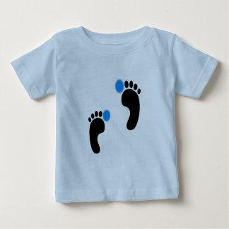 Os pés do bebê multam o t-shirt do jérsei
