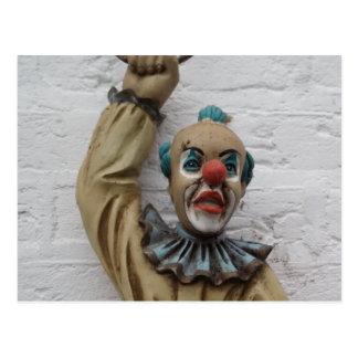 Palhaço engraçado do carnaval que pendura na cartão postal