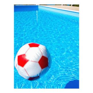 Papel Timbrado Bola de praia que flutua na água na piscina