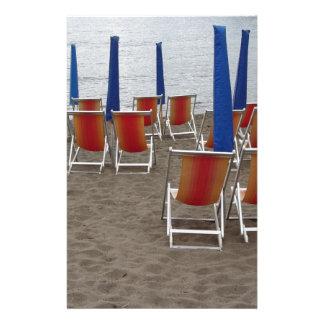 Papelaria Cadeiras de madeira coloridas na praia da areia