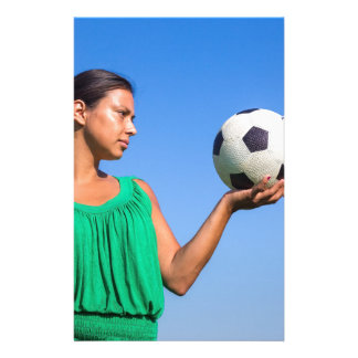 Papelaria Jovem mulher que guardara o futebol na mão com céu