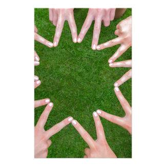 Papelaria Muitos braços das crianças com as mãos que fazem a