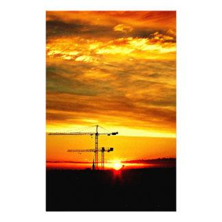 Papelaria Nascer do sol que mostra em silhueta guindastes