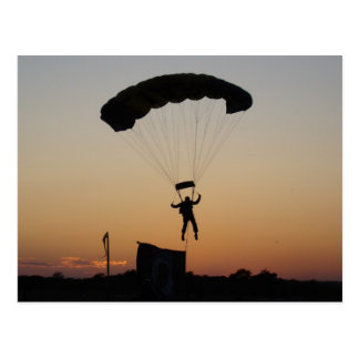 Pára-quedas do Skydiver no cartão do por do sol