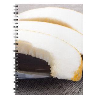 Partes naturais de melão amarelo em uma placa caderno espiral