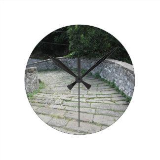 Passagem de pedra da descida da ponte medieval relógio redondo