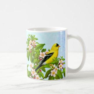Pássaro americano do Goldfinch na caneca da árvore