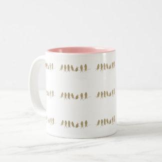 Pássaros bonitos do ouro em uma caneca do chá do