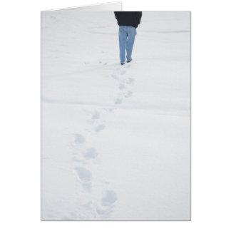 Passos no cartão novo do inverno da neve