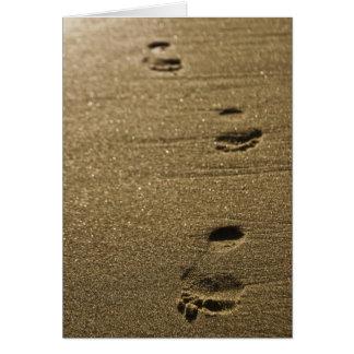 Pegadas no cartão da areia