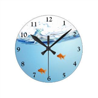 Peixe dourado sob o aquário da água relógio redondo