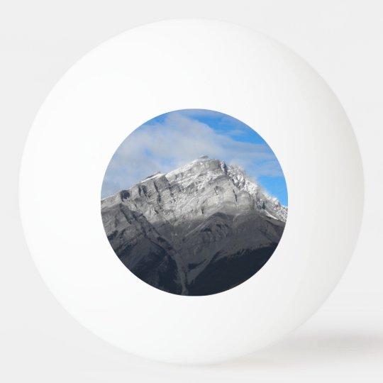 Pico de montanha cinzento, céu azul nebuloso bola de ping-pong