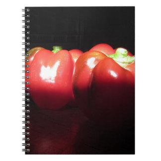 Pimentas vermelhas iluminadas pela luz do sol na caderno espiral