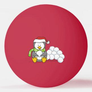 Pinguim do Natal que senta-se com bolas da neve