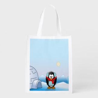 Pinguim nas capas protectoras para as orelhas, no sacolas ecológicas para supermercado
