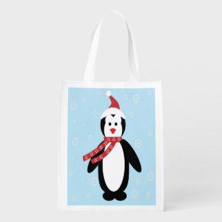 Pinguim que veste o lenço da estrela com flocos de sacola ecológica para supermercado