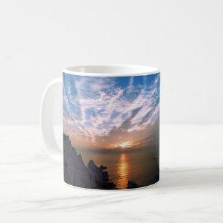 Por do sol sereno sobre a caneca de café da água