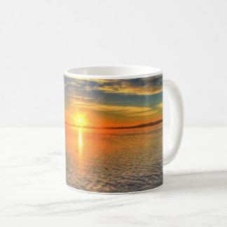 Por do sol sereno sobre a caneca de café do mar