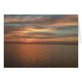 Por do sol sobre o cartão de nota do oceano