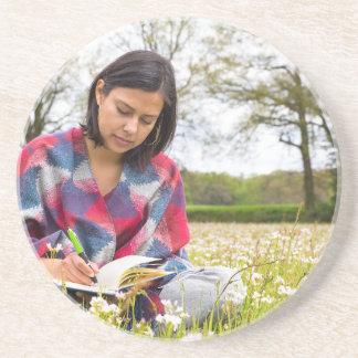 Porta-copos De Arenito Escrita da mulher no prado com flores do primavera