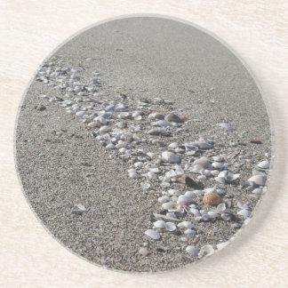Porta-copos Seashells na areia. Fundo da praia do verão
