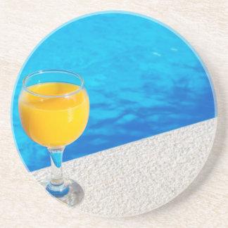 Porta-copos Vidro com sumo de laranja na borda da piscina