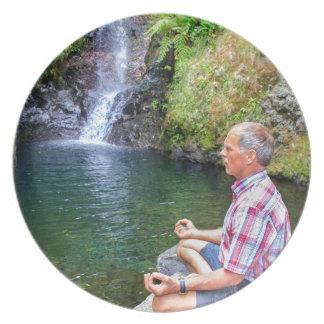 Prato De Festa Homem que senta-se na rocha que meditating perto