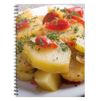 Prato de vegetariano de batatas e da pimenta de cadernos espiral
