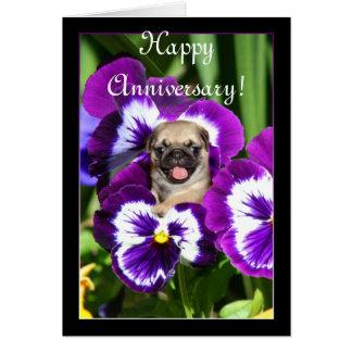 Pug feliz do aniversário no cartão dos pansies