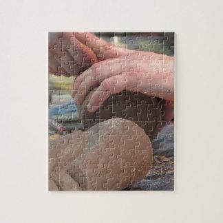 Quebra-cabeça As mãos cortaram uma escultura de um chocolate