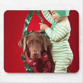 Rapaz pequeno que decora um cão mouse pad