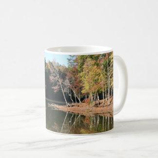 Reflexão do lago das folhas alaranjadas da queda & caneca de café