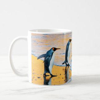 Rei pinguins na caneca do nascer do sol