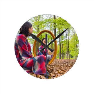 Relógio Redondo A mulher senta-se com o espelho na floresta